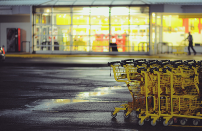 Supermarket carpark at night with trolleys lined up