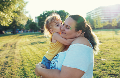 Mother hugging child outdoors