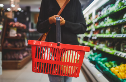 Person holding shopping basket in supermarket